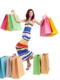 En flicka i en lång klänningfärg med shopping bags Arkivfoto