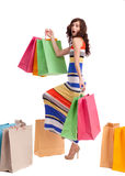 En flicka i en lång klänningfärg med shopping bags Royaltyfri Bild