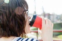 En flicka i en randig T-tröja dricker kaffe Arkivbild