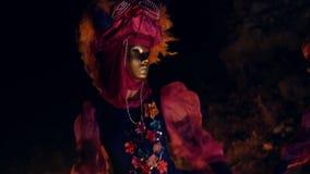 En flicka i enlilor klänning med blommor, en guld- maskering och pärlor runt om hennes hals som dansar vinka hennes händer Natt o arkivfilmer
