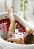En flicka i ett bad med rosa kronblad Ett wellnessbad med rosor arkivfoton