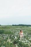 En flicka i ett fält av kamomillar Arkivbild