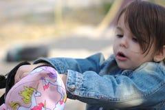 En flicka i ett grov bomullstvillomslag med en svans som ser i en ryggsäck på lekplatsen arkivbild