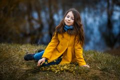 En flicka i ett gult lag i skogen i tidig vår med en pilfilial av ris En flicka som pälsfodrar fresheten eller högt vatten royaltyfria bilder