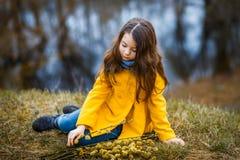 En flicka i ett gult lag i skogen i tidig vår med en pilfilial av ris En flicka som pälsfodrar fresheten eller högt vatten fotografering för bildbyråer