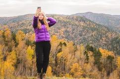 En flicka i ett lila omslag gör en salfi på ett berg, en sikt av bergen och en höstlig skog vid en molnig dag royaltyfria foton