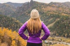 En flicka i ett lila omslag ser ut in i avståndet på ett berg, en sikt av bergen och en höstlig skog vid ett mulet arkivfoto