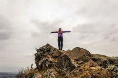 En flicka i ett lila omslag som sträcker hennes armar på ett berg, en sikt av bergen och en höstskog vid en molnig dag Royaltyfria Bilder