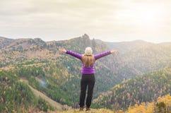 En flicka i ett lila omslag som sträcker hennes armar på ett berg, en sikt av bergen och en höstskog vid en molnig dag Royaltyfri Bild