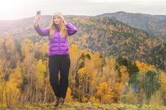 En flicka i ett lila omslag som sträcker hennes armar på ett berg, en sikt av bergen och en höstskog vid en molnig dag Arkivbild