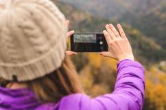 En flicka i ett lila omslag tar bilder på en telefon i bergen, en höstskog med en molnig dag Arkivfoto
