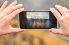 En flicka i ett lila omslag tar bilder på en telefon i bergen, en höstskog med en molnig dag Arkivbilder