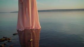 En flicka i ett ljust - rosa klänning i vattnet En flicka i en rosa klänning går till och med vattnet Fridsamt semesterparadis stock video