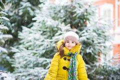 En flicka i ett omslag i vintern jublar i snön, hopp, kast kastar snöboll, körningar i vintern Barns vinterholid royaltyfri foto