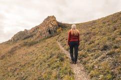 En flicka i ett rött omslag går i bergen, en höstskog med en molnig dag Royaltyfri Foto