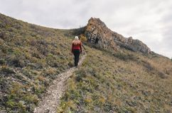En flicka i ett rött omslag går i bergen, en höstskog med en molnig dag Arkivfoto