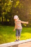 En flicka i ett rosa lock går på trottoarkanten Det exponerar panelljuset arkivfoto