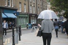 En flicka i ett svartvitt plädmodeomslag under ett genomskinligt paraply mot bakgrunden av London Arkivbilder