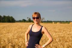 En flicka i ett vetefält arkivfoto