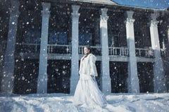 En flicka i ett vit pälslag och krona mot bakgrunden av en gammal byggnad royaltyfria bilder