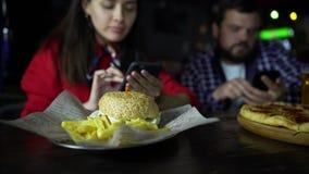 En flicka i företaget av en man som tar bilder på din smartphone din hamburgare på stången lager videofilmer