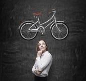 En flicka i formell kläder drömmer om en ny cykel En skissa av en cykel dras på den svarta svart tavlan Arkivfoto