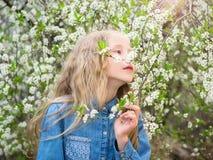 En flicka i en grov bomullstvillskjorta tycker om doften av körsbärsröda blomningar fotografering för bildbyråer