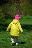 En flicka i en gul regnrock som g?r i skogen royaltyfri bild