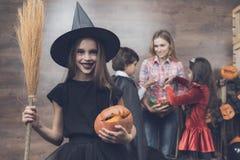 En flicka i en häxadräkt står på bakgrunden av andra barn och en kvinna Flicka som rymmer en kvast och en pumpa Arkivfoton