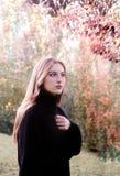 En flicka i höstträdgård royaltyfri foto