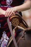 En flicka i klassisk klänning klappar hans häst på bakgrunden av slotten royaltyfri foto