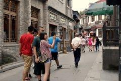 En flicka i Peking hutongs tar foto Fotografering för Bildbyråer