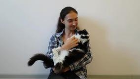 En flicka i en plädskjorta gör tecken åt en fluffig svartvit katt till henne Tar henne i hans armar, kramar och kyssar lyckligt h arkivfilmer