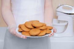 En flicka i plast- handskar rymmer en vit platta med pepparkakan i köket arkivfoto