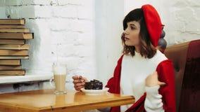 En flicka i en röd basker och en halsduk på hennes skuldror sitter i ett kafé över en kopp kaffe och en kaka stock video