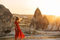 En flicka i en röd klänning i solljuset mot bakgrunden av spetsigt vaggar mycket ljust konstnärligt foto royaltyfria foton