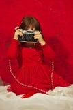 En flicka i rött genom att använda en tappningfotokamera Arkivfoto