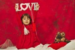 En flicka i rött innehav ett förälskelsetecken Royaltyfri Bild