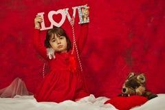 En flicka i rött innehav ett förälskelsetecken Royaltyfria Bilder