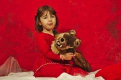 En flicka i rött krama en liten dålig vargdocka Royaltyfri Fotografi