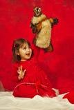 En flicka i rött krama en liten dålig vargdocka Royaltyfria Bilder