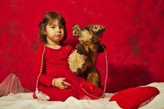 En flicka i rött krama en liten dålig vargdocka Arkivfoto