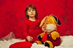 En flicka i rött spela med den välfyllda kaninleksaken Arkivbilder