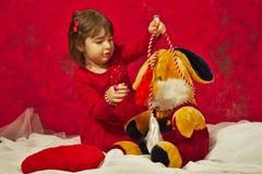 En flicka i rött spela med den välfyllda kaninleksaken Arkivfoton