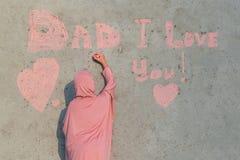 En flicka i en rosa hijab med krita skriver på väggfarsan som jag älskar dig Begrepp av den lyckliga faderdagen royaltyfria bilder