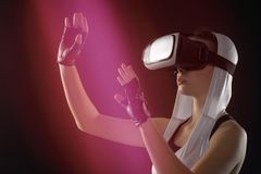 En flicka i silverkläder med en huv ser in i virtuell verklighet Royaltyfria Foton