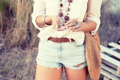 En flicka i stilen av en hippie i prydnader, bochosstilen håller ett skal av sniglar i hennes händer Tappningfärgsignal Royaltyfri Fotografi