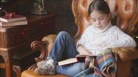 En flicka i en stucken vit tröja läser saga lager videofilmer