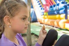 En flicka i trampolin parkerar tuggor en lever på en bänk royaltyfria foton
