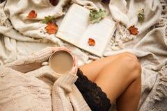 En flicka i en varm tröja sitter på en beige woolen filt och rymmer rånar av varmt kaffe i hennes händer Höstlivstail hem- comfor royaltyfria foton